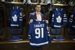 John Tavares holds up a Maple Leafs jersey in the Maple Leafs' locker room following a news conference in Toronto, Sunday July 1, 2018. Tavares is going home, agreeing to terms on a $77 million, seven-year contract with his childhood team. (Chris Young/The Canadian Press via AP)