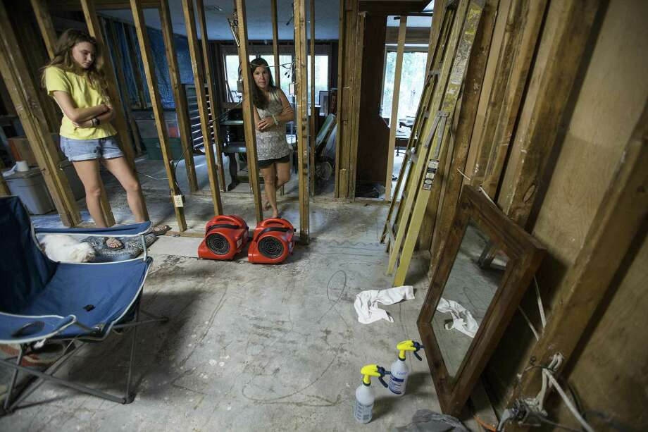 Clair Slaughter and her mother, Amy, stand inside their flood-damaged home, with the flood line seen on the wall to the right, as they rebuild, on Thursday, June 28, 2018, in Kingwood. The Slaughters are in favor of a project to dredge a large sandbar in the San Jacinto River, to help alleviate flooding in Kingwood. They are still recovering from the floodwaters from Hurricane Harvey, where they had 52 inches of water inside their home. Photo: Brett Coomer, Staff / Houston Chronicle / © 2018 Houston Chronicle