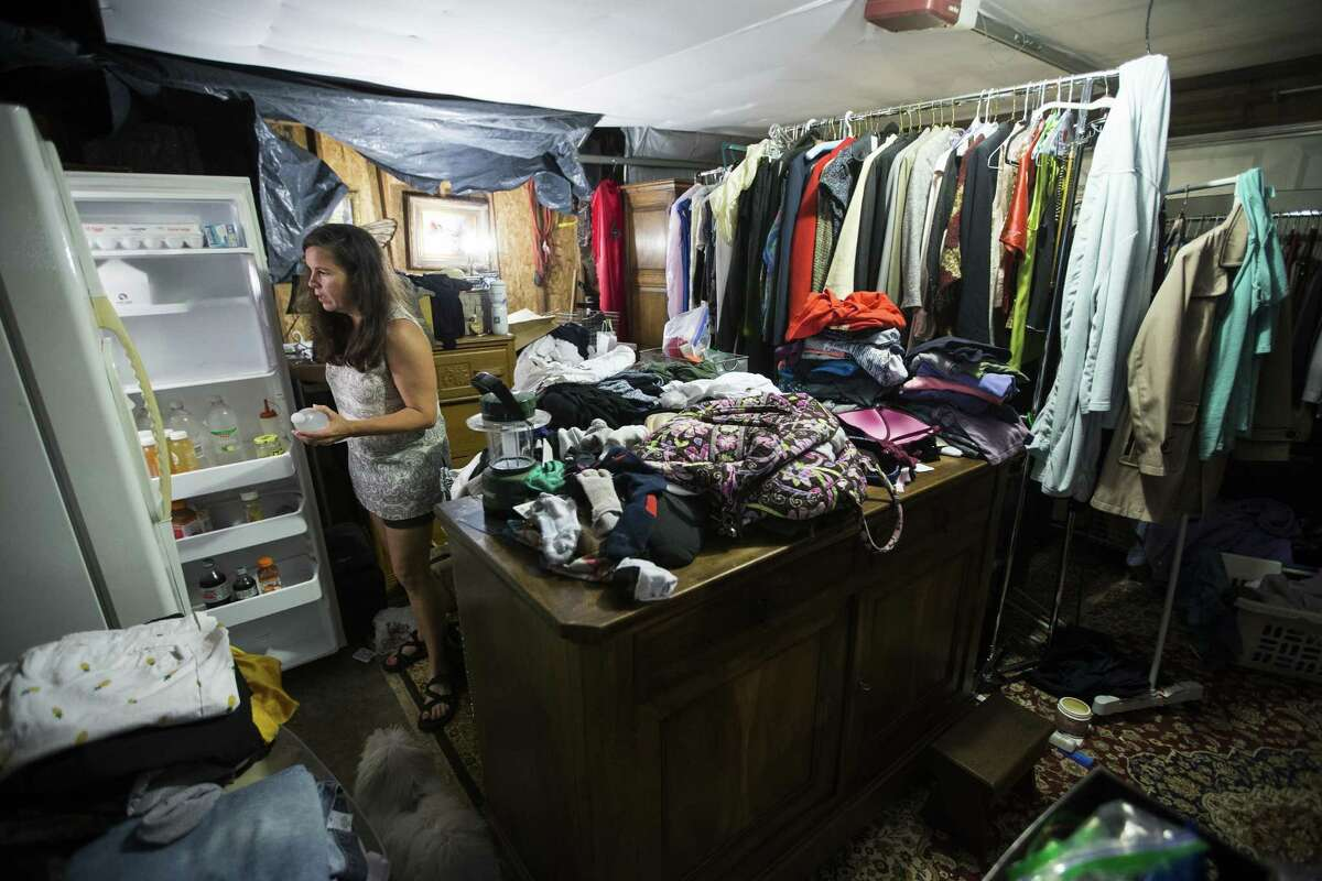 Amy Slaughter gets a bottle of water in her garage, which has been converted into a pantry and closet, as her family continues to rebuild their flood-damaged home, on Thursday, June 28, 2018, in Kingwood. The Slaughters are in favor of a project to dredge a large sandbar in the San Jacinto River, to help alleviate flooding in Kingwood. They are still recovering from the floodwaters from Hurricane Harvey, where they had 52 inches of water inside their home.