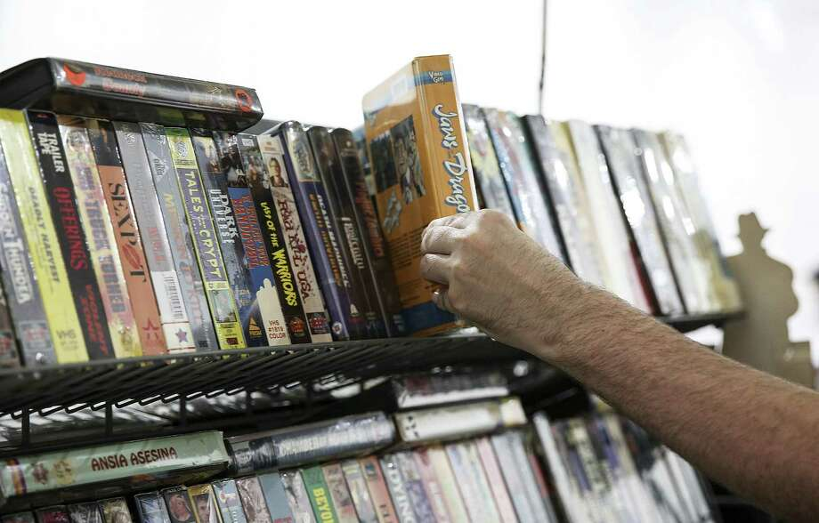 An attendees of Insomnia Gallery's third VHS Swap checks out a VHS tape from the booth of Video Sanctum on Sunday, July 1, 2018 in Houston.  (Elizabeth Conley/Houston Chronicle) Photo: Elizabeth Conley, Staff / Houston Chronicle / ©2018 Houston Chronicle