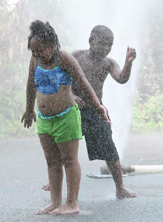 Zamorah Jackson age 8 years ,left, and Claydale Slaughter age 6 years of Troy, N.Y., take advantage of a sprinkler set up next to the Canal Street Park by the Troy Fire Department to help people cool off during super hot weather Sunday, July 1, 2018, in Troy, N.Y. (Hans Pennink / Special to the Times Union) Photo: Hans Pennink / Hans Pennink