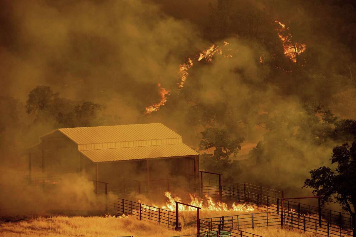 Flames rise around an outbuilding as the County fire burns in Guinda, Calif., Sunday July 1, 2018. Evacuations were ordered as dry, hot winds fueled a wildfire burning out of control Sunday in rural Northern California, sending a stream of smoke some 75 miles south into the San Francisco Bay Area.
