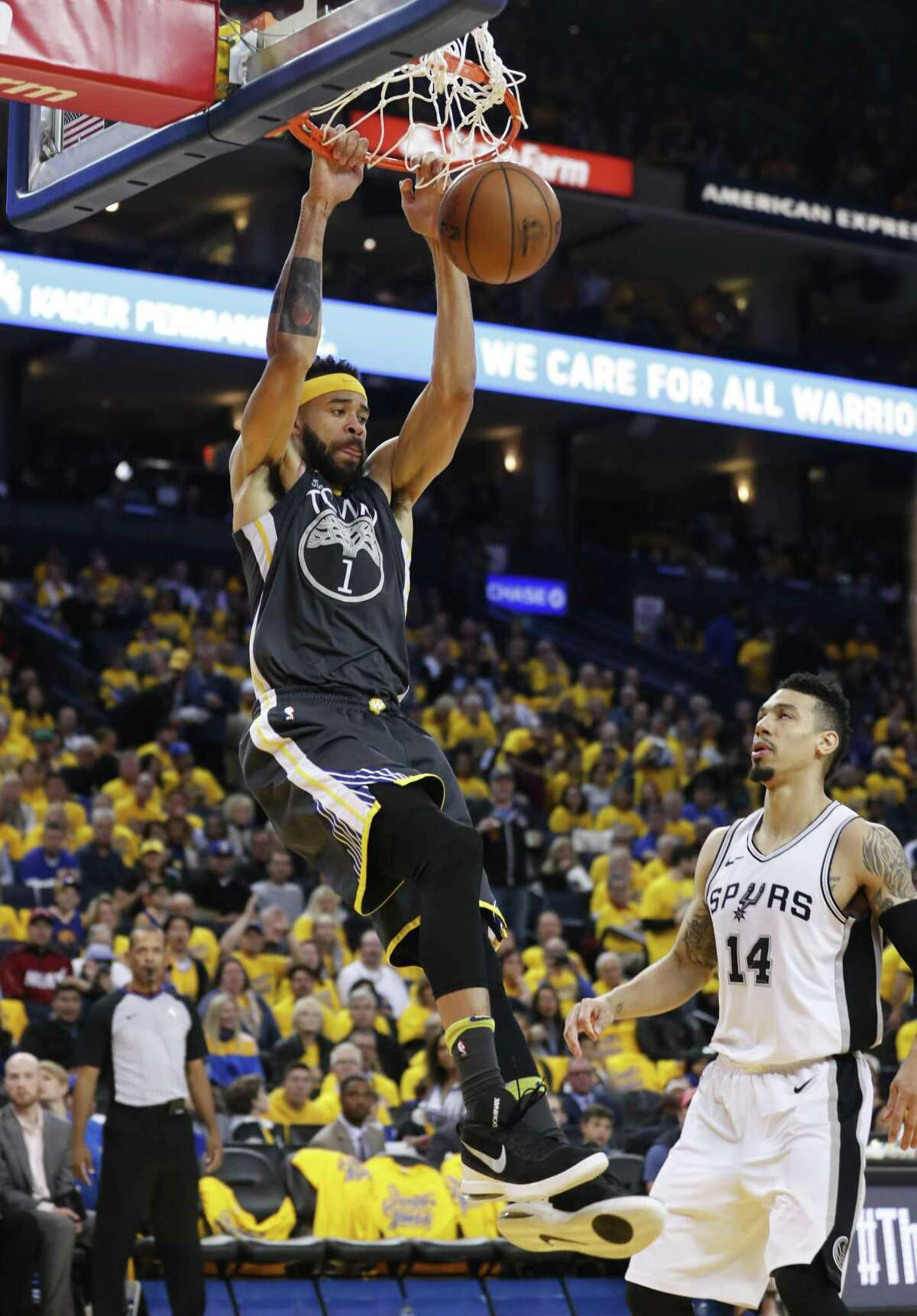 Golden State Warriors' JaVale McGee dunks over San Antonio Spurs' Danny Green in the third quarter during game 2 of round 1 of the Western Conference Finals at Oracle Arena on Monday, April 16, 2018 in Oakland, Calif.