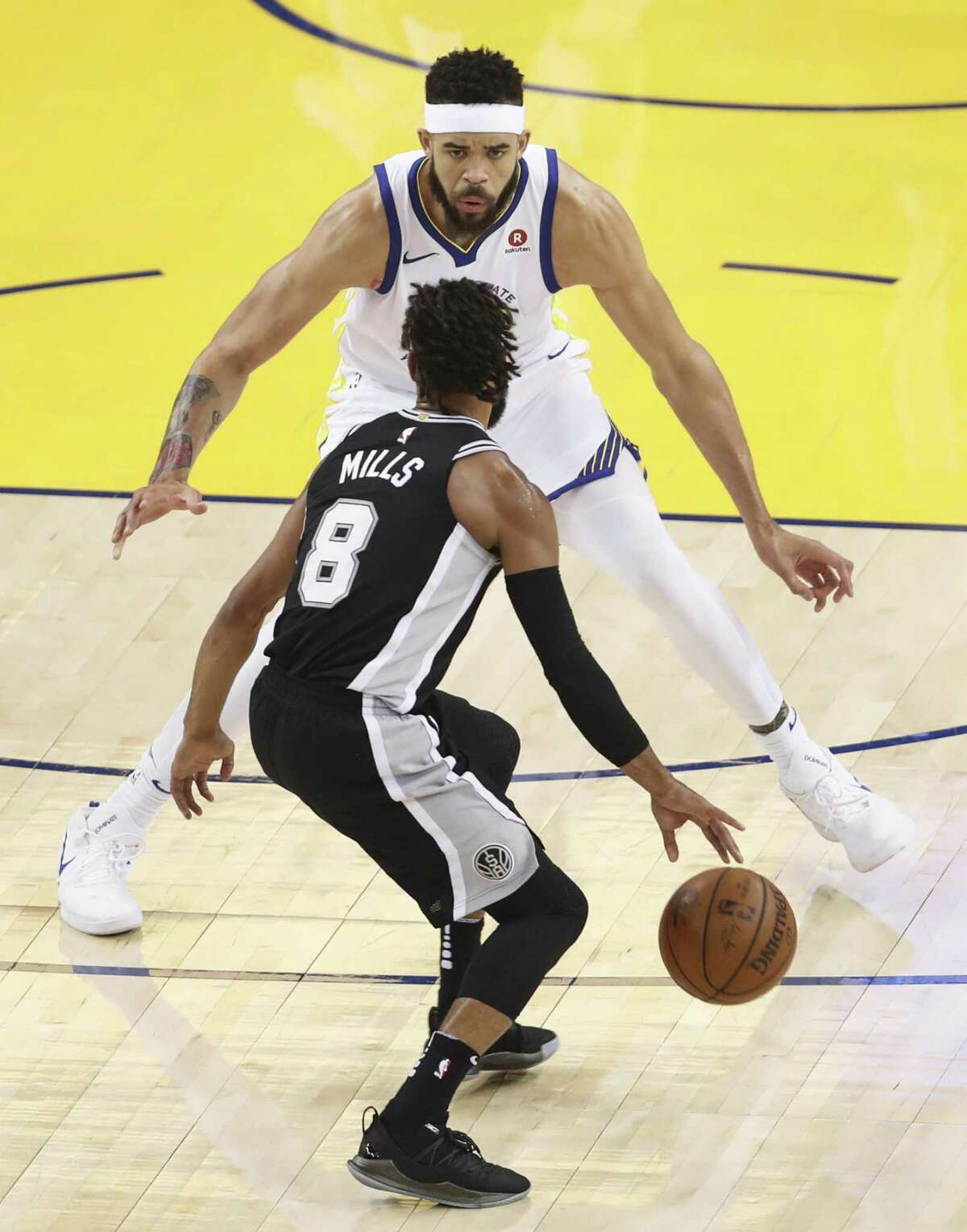 Golden State Warriors' JaVale McGee guards San Antonio Spurs' Patty Mills in the first quarter during game 1 of round 1 of the Western Conference Finals at Oracle Arena on Saturday, April 14, 2018 in Oakland, Calif.