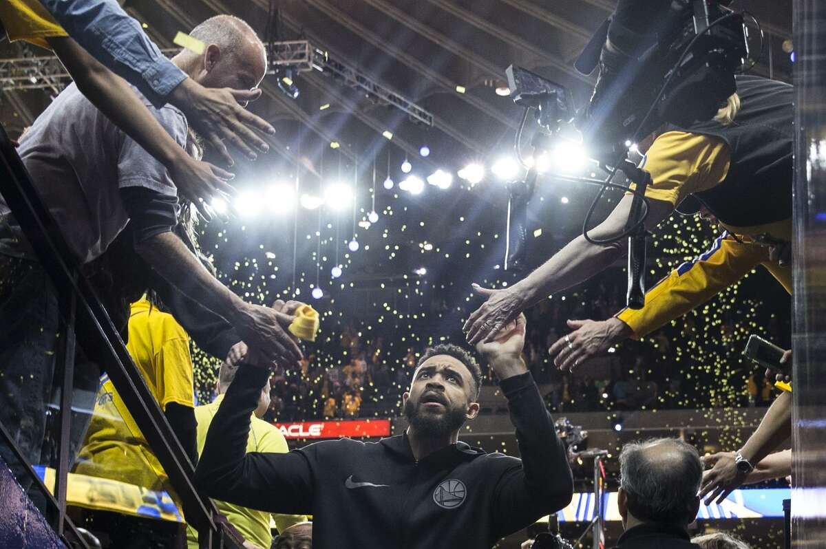 Warriors' JaVale McGee greets fans as confetti rains down after the Golden State Warriors defeated the San Antonio Spurs 116-101 in the second game of the NBA Playoffs at Oracle Arena Monday, April 16, 2018 in Oakland, Calif.