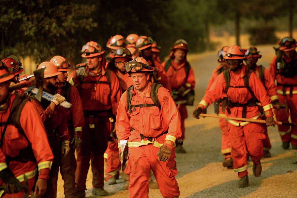 Inmate firefighters leave an assignment while battling a wildfire in Guinda, Calif., Sunday July 1, 2018. Evacuations were ordered as dry, hot winds fueled a wildfire burning out of control Sunday in rural Northern California, sending a stream of smoke some 75 miles (120 kilometers) south into the San Francisco Bay Area.
