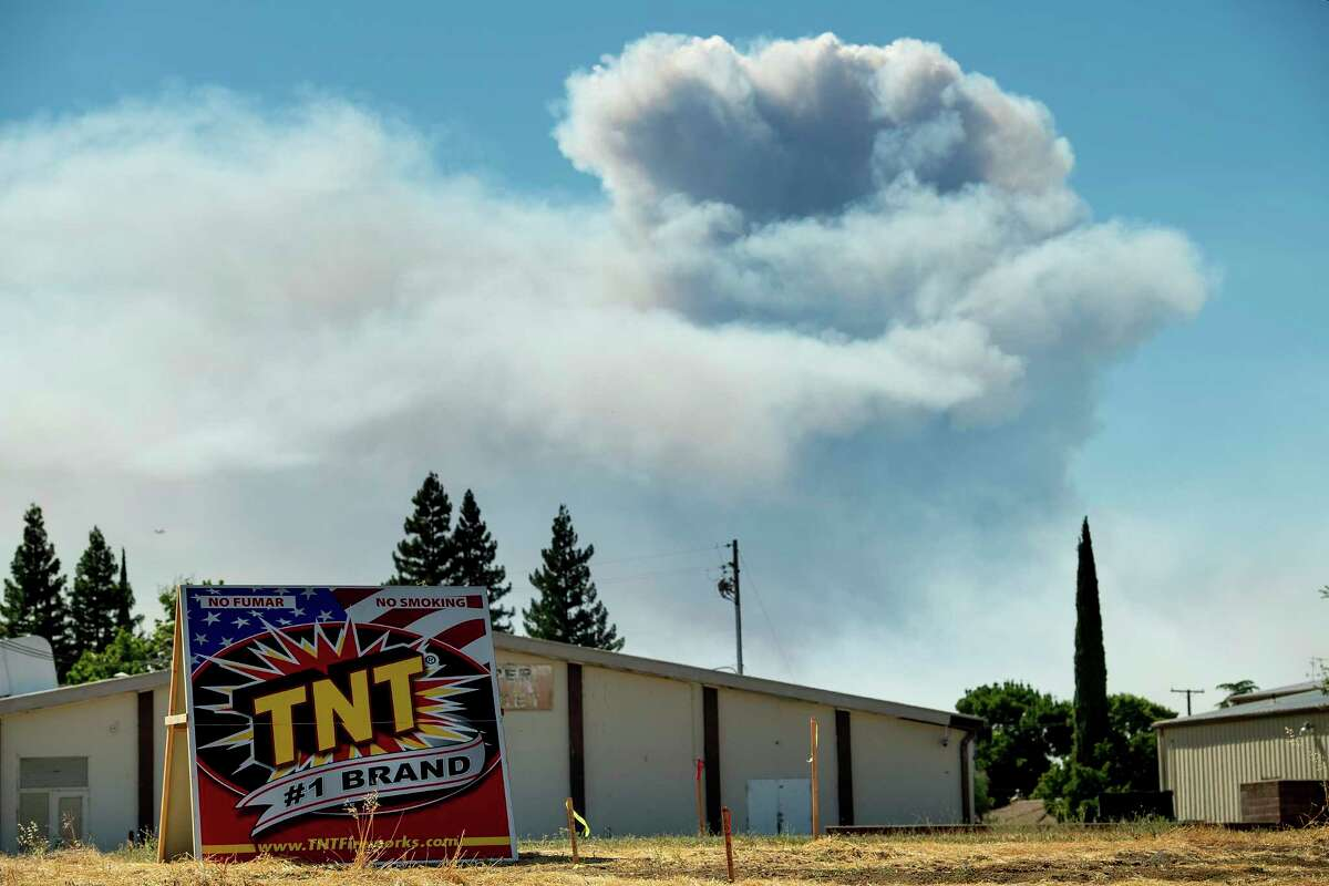 A plume rises behind a building in Esparto, Calif., as a wildfire burns on Sunday, July 1, 2018. Evacuations were ordered as dry, hot winds fueled a wildfire burning out of control Sunday in rural Northern California, sending a stream of smoke some 75 miles (120 kilometers) south into the San Francisco Bay Area.