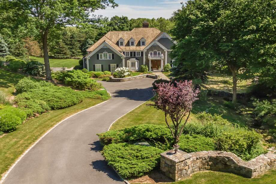 The gray custom-built colonial house at 1 Spruce Meadow Court sits on a 2.23-acre largely level property; a tranquil park-like setting.