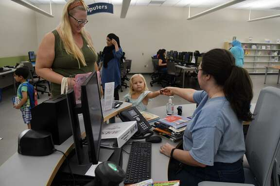 Kennedy Tomsa, 3, center, with her mom Amy, of Spring, hands her library card to Assistant Branch Manager Christie Yerby, right, while checking out her books during their visit to Barbara Bush Branch Library in Spring on June 27, 2018. (Jerry Baker/For the Chronicle)