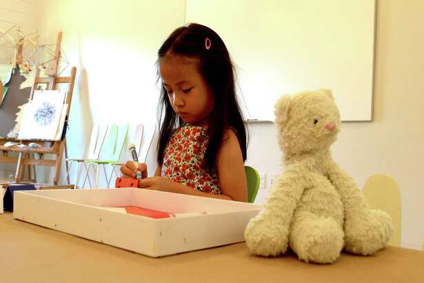 Bella Zhou, 5, of Stamford colors her project at the Open Arts Studio class on Saturday, June 30, 2018, at Grace Farms in New Canaan, Conn.