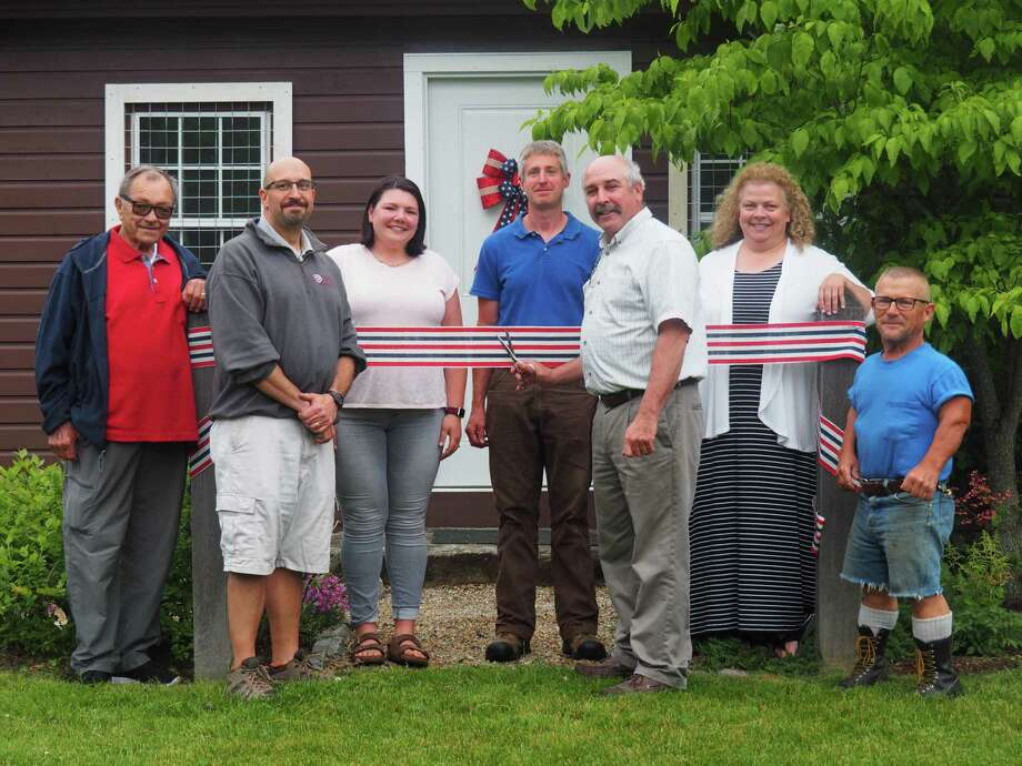 Residents recently celebrated the renovations of the bathrooms at Camp Cochipianee in Goshen. First Selectman Bob Valentine, center right, joined other town officials and residents for the ribbon cutting. Photo: Contributed Photo /