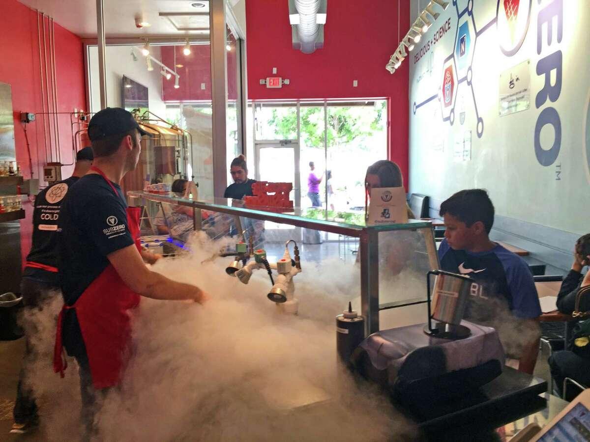 A young customer watches as a server blasts liquid nitrogen to create a tasty treat at Sub Zero Nitrogen Ice Cream in Sugar Land.