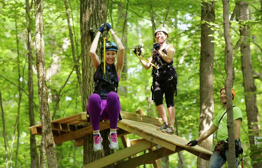The Times Union's Kristi Barlette, left, makes her way down a zipline at the Mountain Ridge Adventure ropes course as the Times Union's Sara Tracey waits her turn on Monday, June 18, 2018, in Schenectady, N.Y. (Paul Buckowski/Times Union)