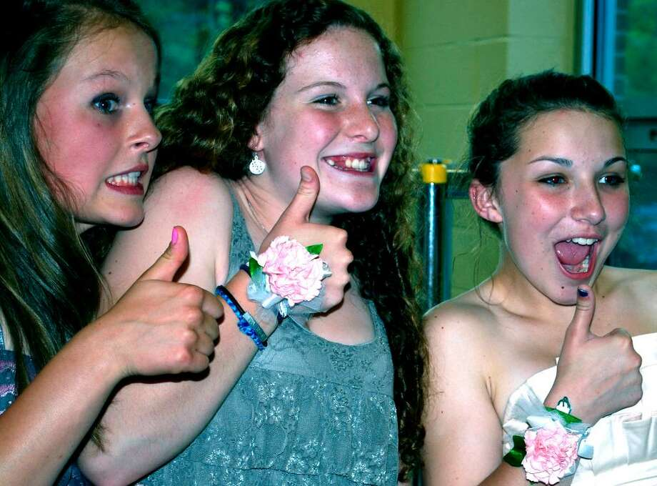 "SPECTRUM/Kent Center School eighth-grade graduates, from left to right, Laura Craft, Emma Hannan and Kori Rimany, signal ""thumbs up"" to one of their parents capturing their giddiness on film at the reception following the school's eighth-grade graduation, June 14, 2010. Photo: Deborah Rose / The News-Times"