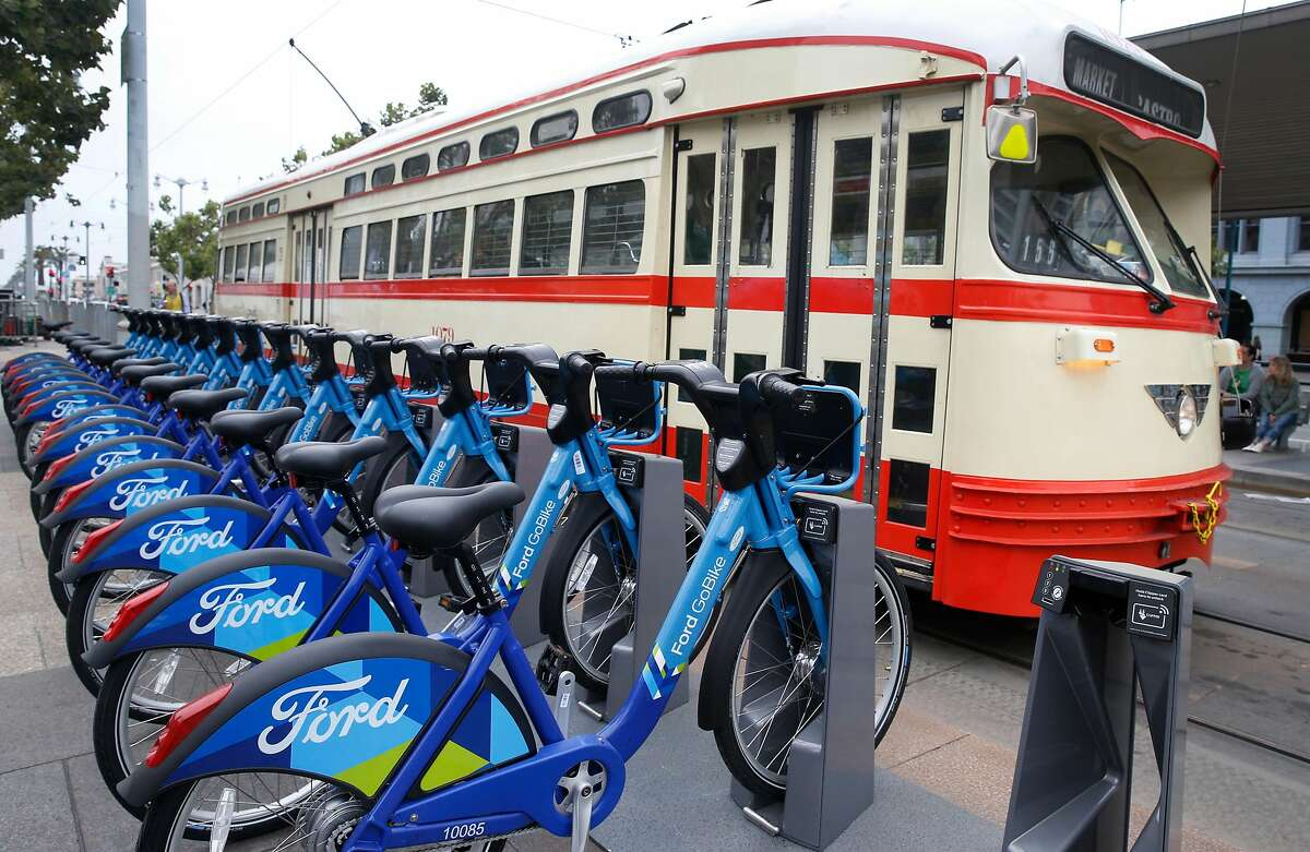 A Muni streetcar rolls past a fleet of Ford GoBike bicycles docked in front of the Ferry Building in San Francisco, Calif. on Wednesday, June 28, 2017. The Bay Area-wide bike sharing service, which plans a fleet of 3,500 bicycles by Labor Day and as many as 7,000 by the end of 2018, went into service today.