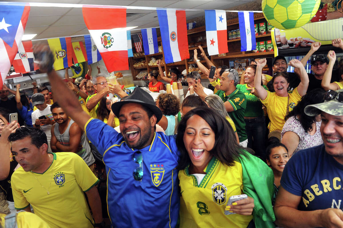 Cesar Macedo and Naomi Garcia celebrate with others at Padaria Minas Bakery, in Bridgeport, Conn. following a goal scored by the Brazilian national football team during the FIFA World Cup soccer game broadcast from Russia July 2, 2018. Brazil defeated Mexico on Monday to advance to the tournament's quarter-final round.