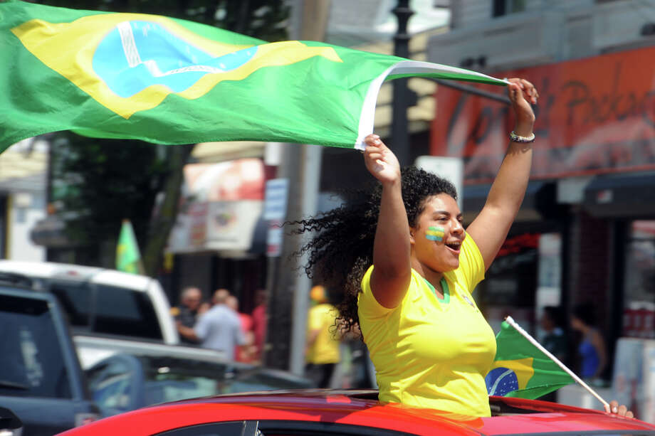 A woman celebrates with a Brazilian flag as the celebration takes to the