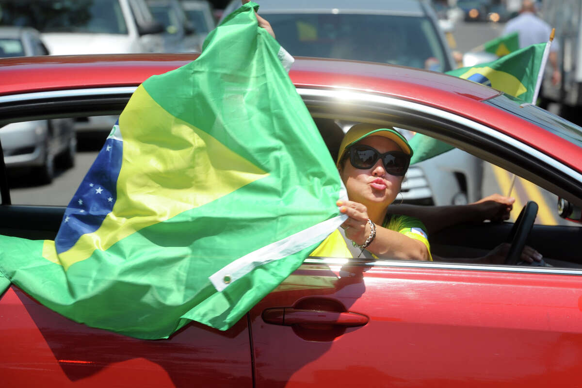 A woman celebrates with a Brazilian flag as the celebration takes to the streets on Bridgeport, Conn. following the Brazilian national football team's victory over Mexico in a FIFA World Cup soccer game in Russia July 2, 2018.