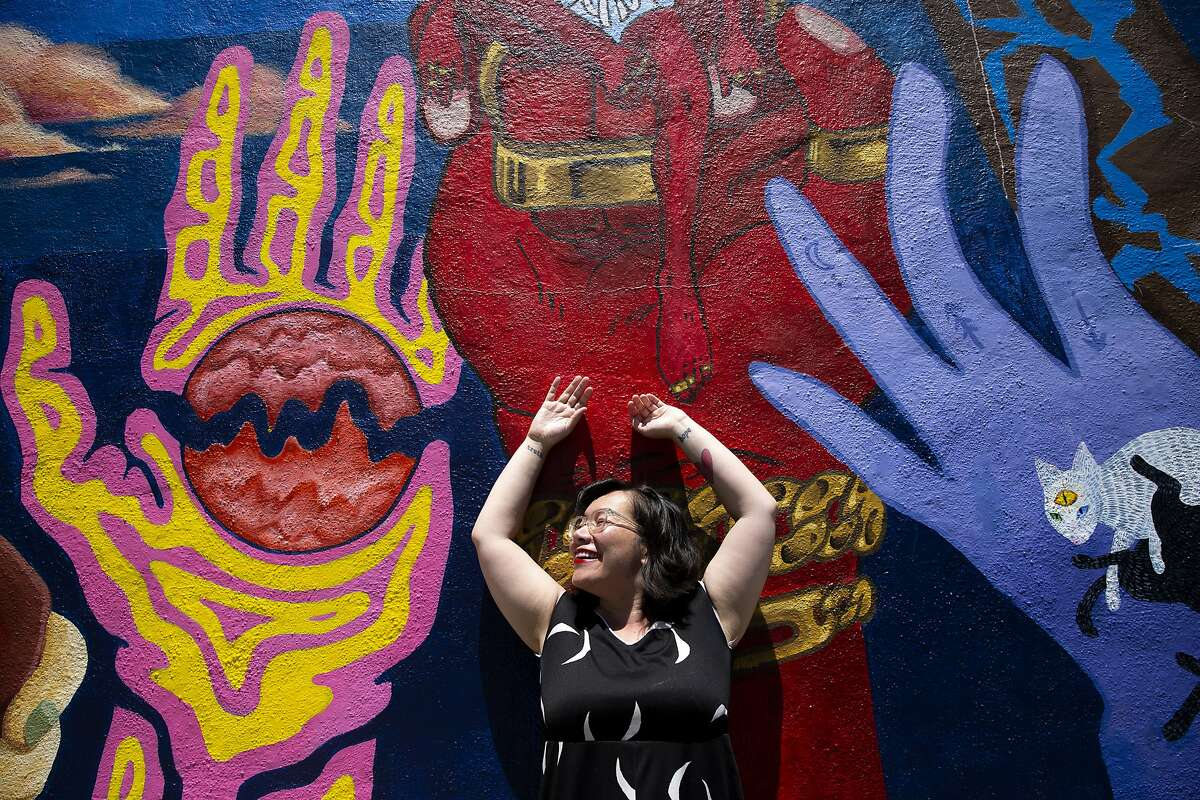 Celeste Chan throws her hands up to mirror the mural as she bathes in the sun, Saturday, June 30, 2018, in Oakland, Calif.