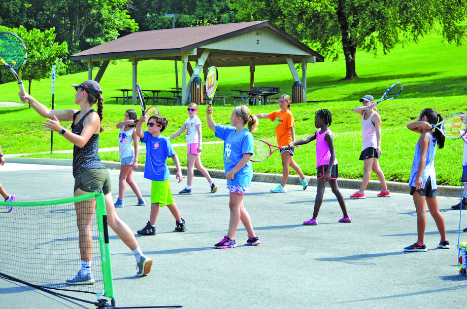 Grace Desse, left, a 2018 Edwardsville High School graduate, leads campers in a drill during Monday's free EHS tennis clinic at Miner Park in Glen Carbon.