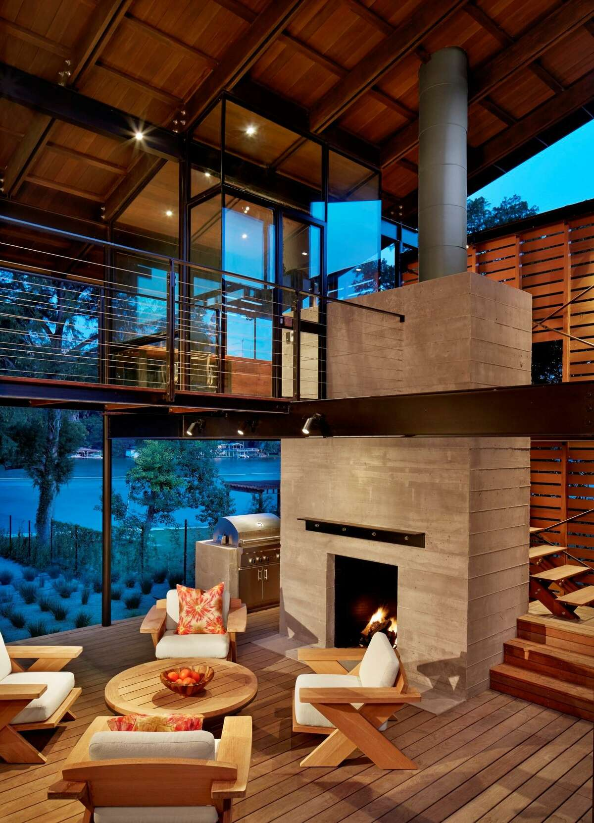 This backyard kitchen has two levels, the lower for cooking and entertaining, the upper, a glassed-in office for working with a view. The board-formed concrete fireplace is topped with a simple angled steel mantle. The lower room is open-air to catch the lake breezes and the furnishings are from Sutherland.