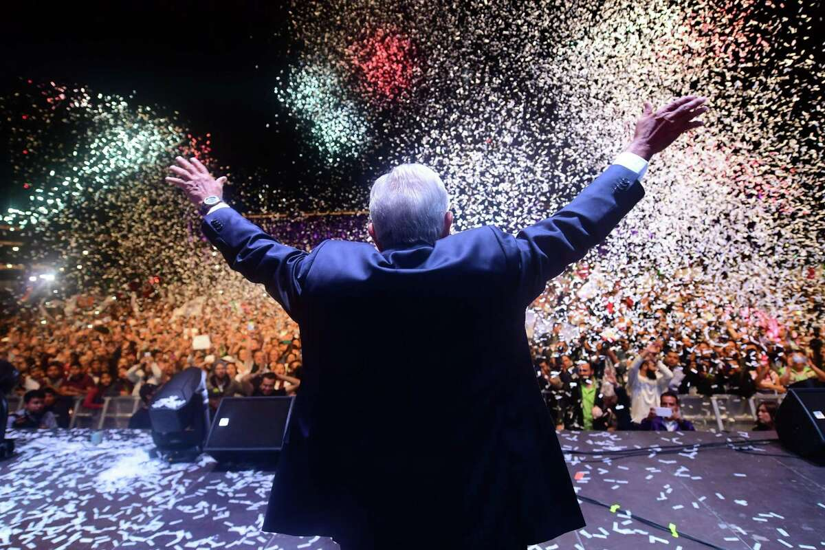"""Newly elected Mexico's President Andres Manuel Lopez Obrador (C), running for """"Juntos haremos historia"""" party, cheers his supporters at the Zocalo Square after winning general elections, in Mexico City, on July 1, 2018."""