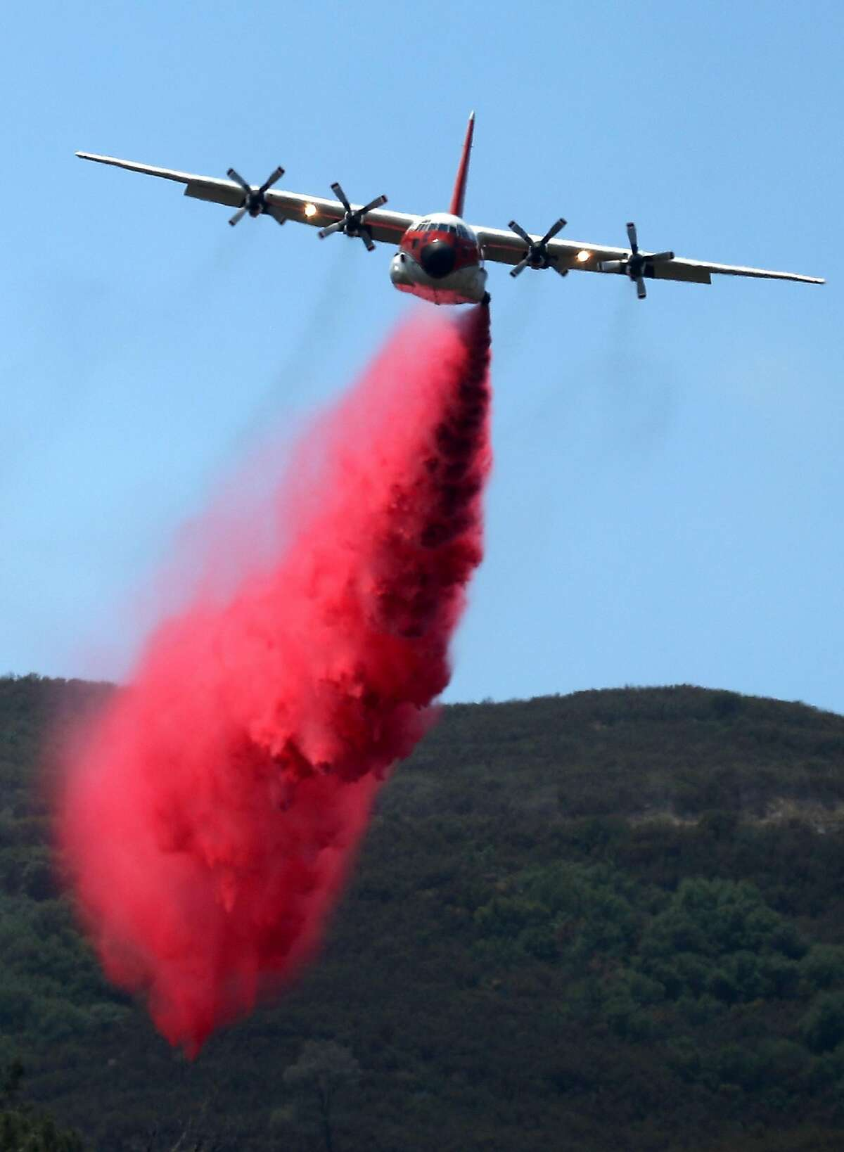 A firefighting air tanker drops Foscheck fire retardant on a hillside ahead of the County Fire on July 2, 2018 in Guinda, California. The fast moving County Fire, that started on Saturday afternoon, has scorched nearly 45,000 acres as it continues to burn through dry grass and brush.