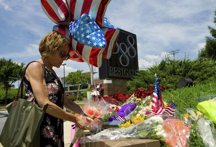 "An Annapolis, Md., resident leaves flowers at a makeshift memorial outside the building housing the Capital Gazette newspaper, where five people were shot and killed. It was too easy to wonder, ""Had Trump finally reached someone who would act out his hatred of the media?"" Photo: Jose Luis Magana /Associated Press / Copyright 2018 The Associated Press. All rights reserved"