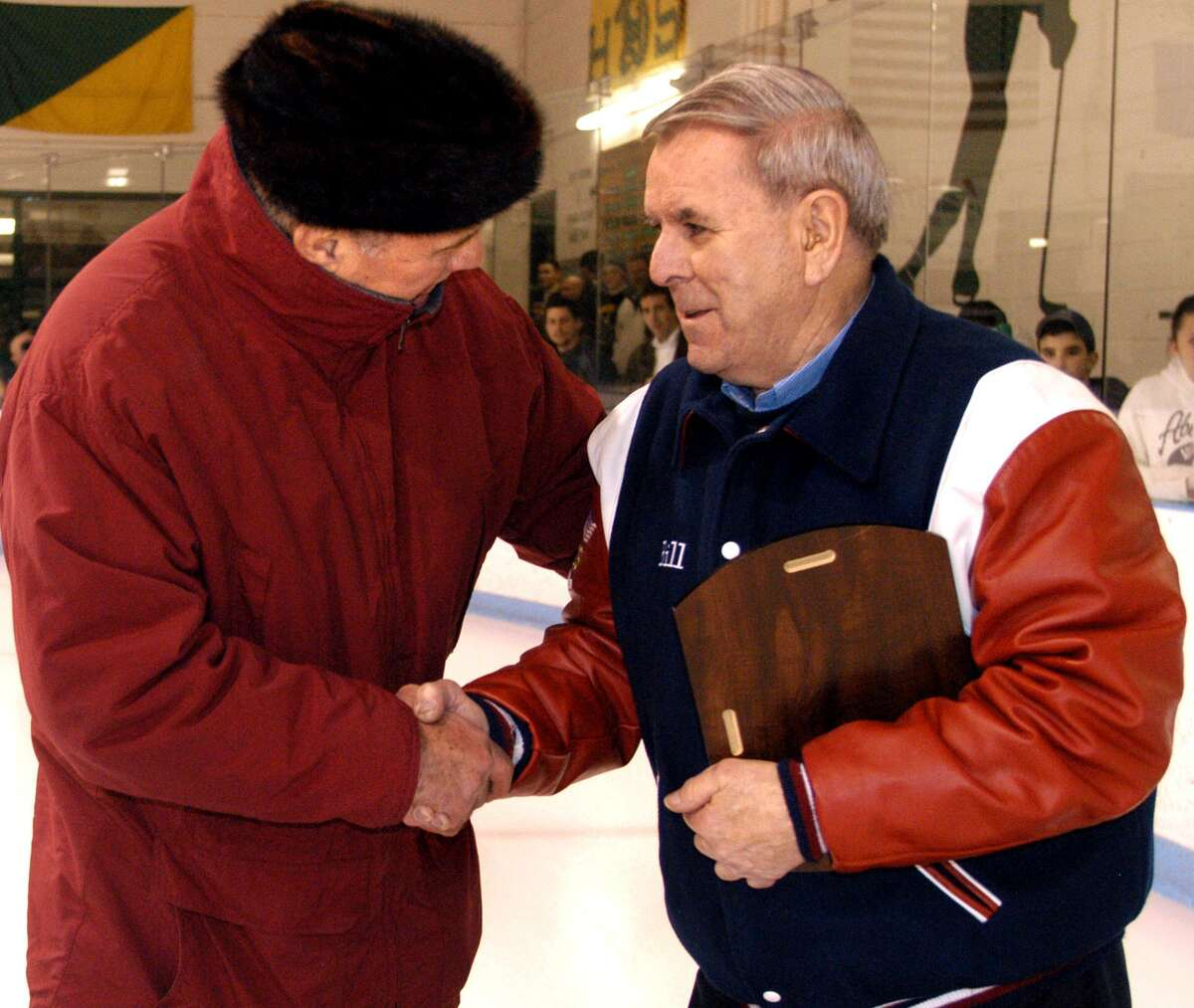 Dick Gagliardi, left, shakes hands with Bill Belisle after the two the two former coaches were honored at a ceremony preceding a Hamden-Mount St. Charles hockey game in Hamden.