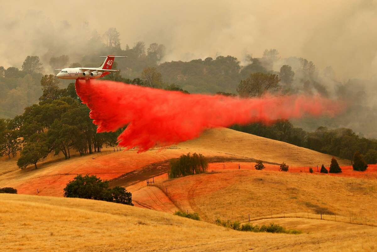 A plane dumps retardant near a house as the County Fire burns west of Esparto, Calif. on Monday, July 2, 2018.