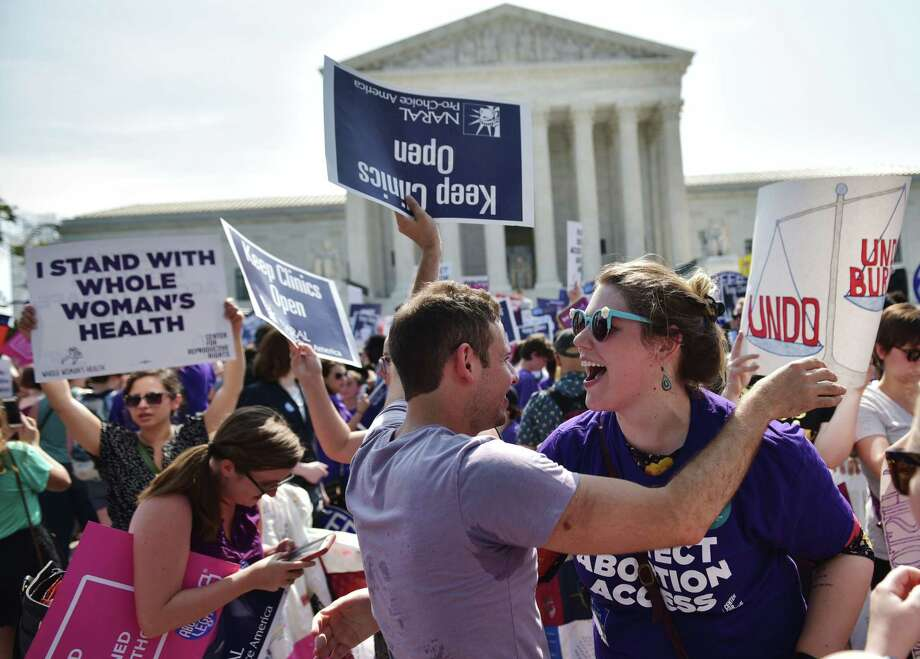 (FILES) In this file photo taken on June 27, 2016 abortion rights activists embrace after the US Supreme Court struck down a Texas law placing restrictions on abortion clinics, outside of the Supreme Court in Washington, DC. Access to abortion and health care will be at the heart of the looming battle over the appointment of a new Supreme Court justice, with all eyes on a handful of senators with the power to endorse, or block, President Donald Trump's choice. Democrats are hoping to prevent Trump from tilting the court to the hard right by tapping an ultra-conservative to replace Justice Anthony Kennedy, the tie-breaking vote between the liberals and conservatives on the nine-seat bench who retires at the end of July.  / AFP PHOTO / MANDEL NGANMANDEL NGAN/AFP/Getty Images Photo: MANDEL NGAN, Contributor / AFP/Getty Images / AFP or licensors