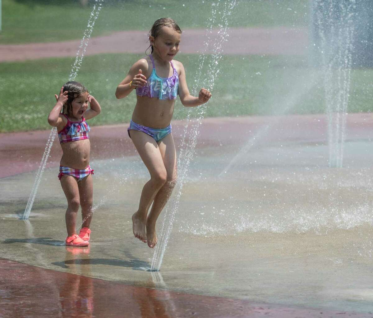 Shiela Gunderson, 7, of Lake George tries her dance steps in the spray pool at the Lake Avenue playground much to the amazement of a fellow water enthusiast Monday July 2, 2018 in Saratoga Springs, N.Y. (Skip Dickstein/Times Union)