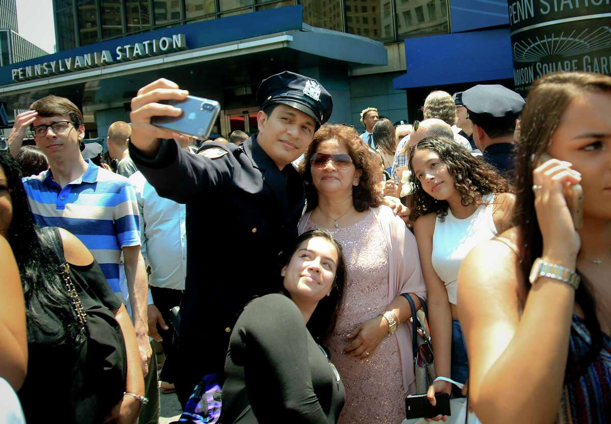 """Police Officer Carlos Villacis Diaz, 23, from Guayaquil, Ecuador, makes a selfie with his family after New York Police Academy's graduation ceremony for 726 new NYPD police officers, from more than 41 countries, Monday July 2, 2018, in New York. """"It's a great moment in my life,"""" said Diaz. """"I am happy to be sharing it with family and friends."""" (AP Photo/Bebeto Matthews)"""