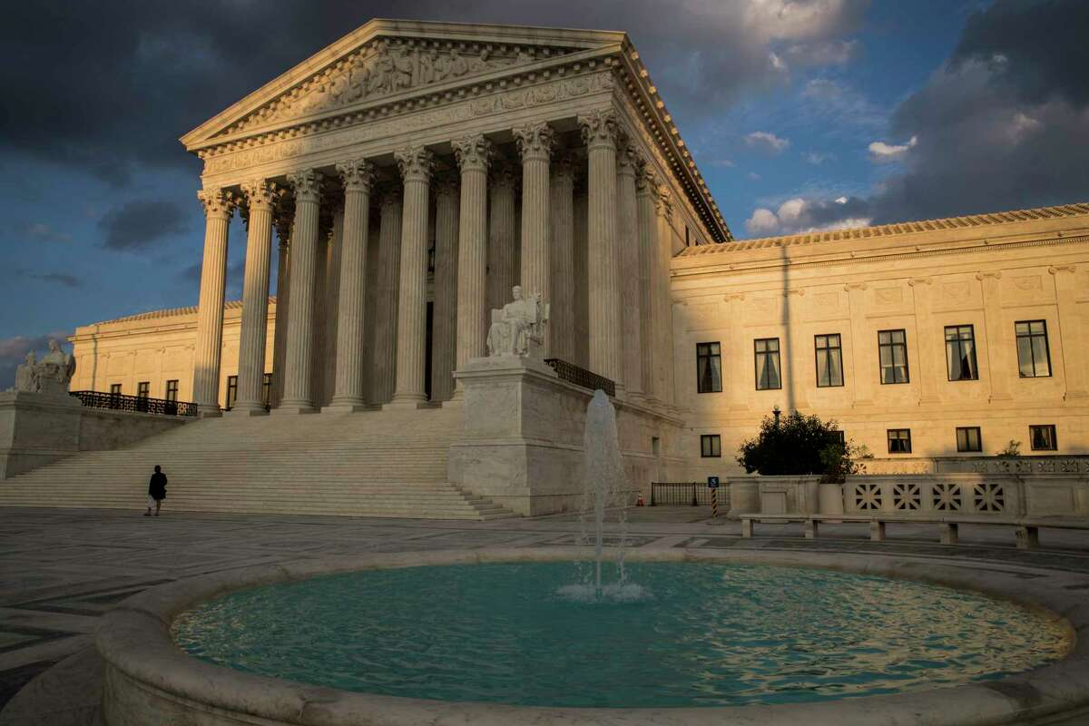 FILE - In this Oct. 10, 2017 file photo, the Supreme Court in Washington is seen at sunset. In a 5-4 decision Friday, The Supreme Court says police generally need a search warrant if they want to track criminal suspects' movements by collecting information about where they've used their cellphones. (AP Photo/J. Scott Applewhite)