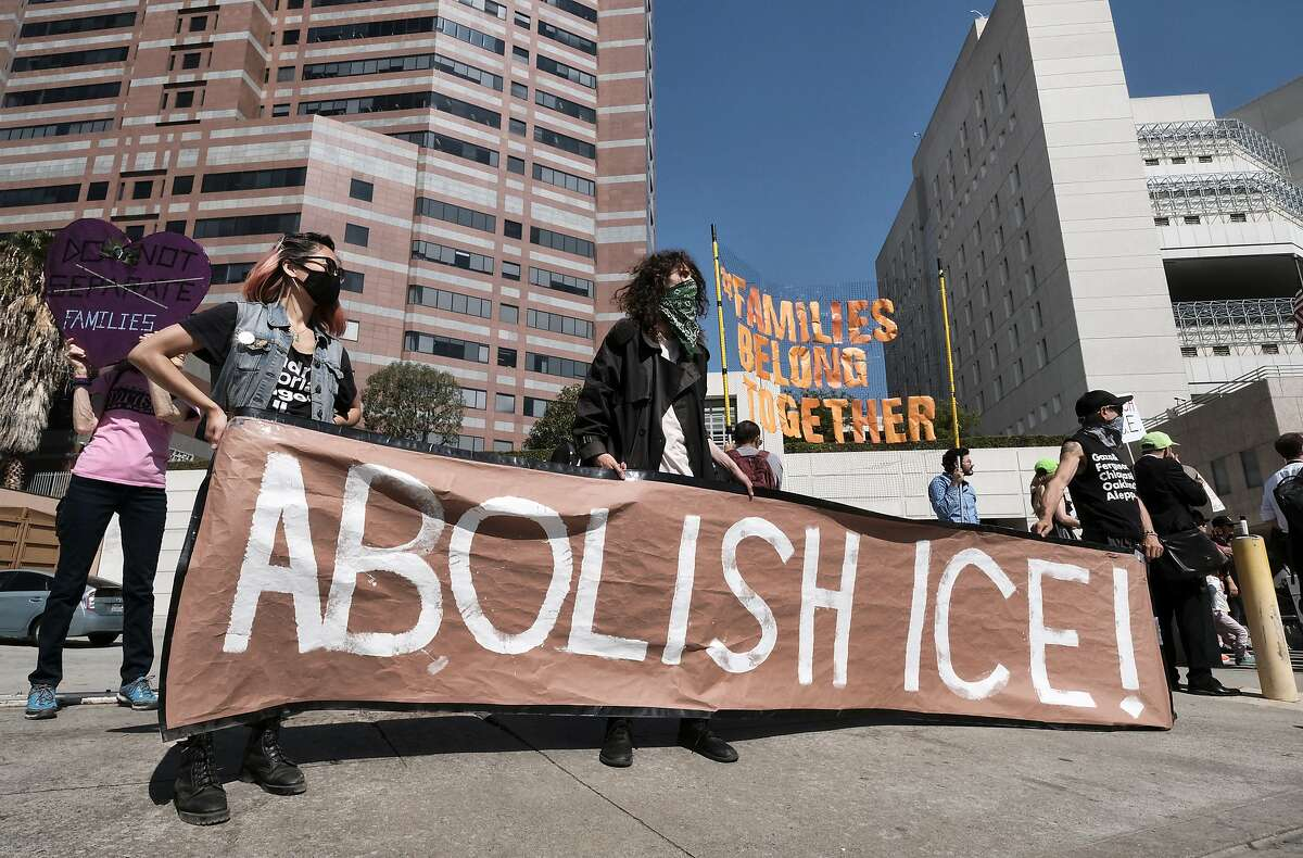 """Protesters display a sign that reads """"Abolish ICE"""" during a rally in front of the Immigration and Customs Enforcement facility in downtown Los Angeles on Monday, July 2, 2018. Protesters who were blocking the entrance to an Immigration and Customs Enforcement facility in downtown Los Angeles have been led away in handcuffs. A group of 17 protesters sat down in the street, blocking the entrance to the facility Monday morning. The protesters, including faith and community leaders, locked arms and chanted, """"Shut down ICE!"""" (AP Photo/Richard Vogel)"""