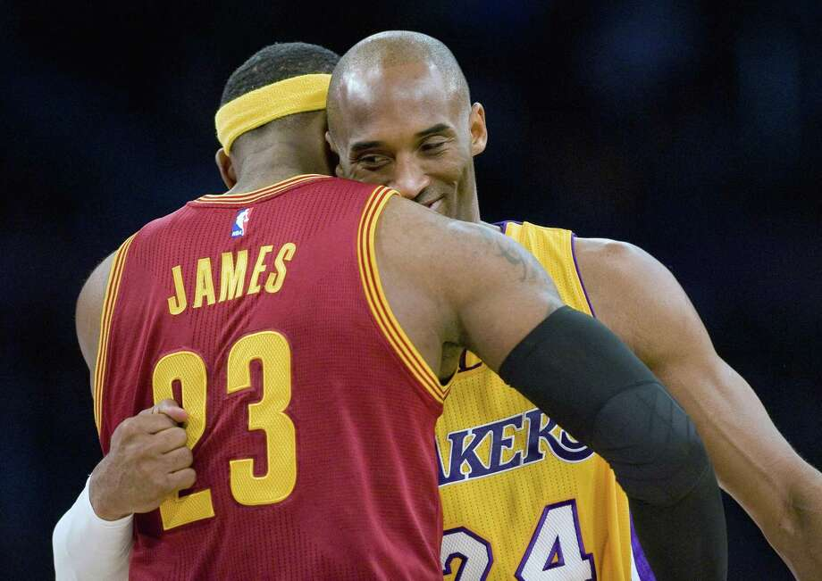 "FILE - In this Jan. 15, 2015, file photo, Los Angeles Lakers guard Kobe Bryant, right, and Cleveland Cavaliers forward LeBron James hug before the start of an NBA basketball game, in Los Angeles. The Los Angeles Lakers have a new superstar — L.A.-Bron. The four-time NBA MVP announced Sunday night, July 1, 2018, that he has agreed to a four-year, $154 million contract with the Lakers. ""Welcome to the family (at)KingJames,"" Bryant said on Twitter . ""(hash)lakers4life (hash)striveforgreatness."" (Paul Rodriguez/The Orange County Register via AP, FIle) Photo: PAUL RODRIGUEZ,, MBI / Associated Press / The Orange County Register"