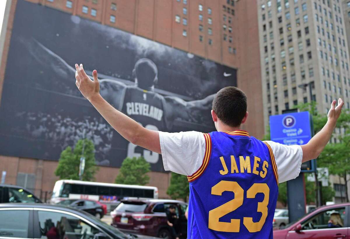 FILE - In this June 9, 2017, file photo, Cleveland Cavaliers fan Jordan Phillips poses for a photo in front of a poster featuring Cleveland Cavaliers forward LeBron James, before Game 4 of the basketball's NBA Finals between the Cavaliers and the Golden State Warriors, in Cleveland. The four-time NBA MVP announced Sunday night, July 1, 2018, that he has agreed to a four-year, $154 million contract with the Los Angeles Lakers. (AP Photo/David Dermer, File)