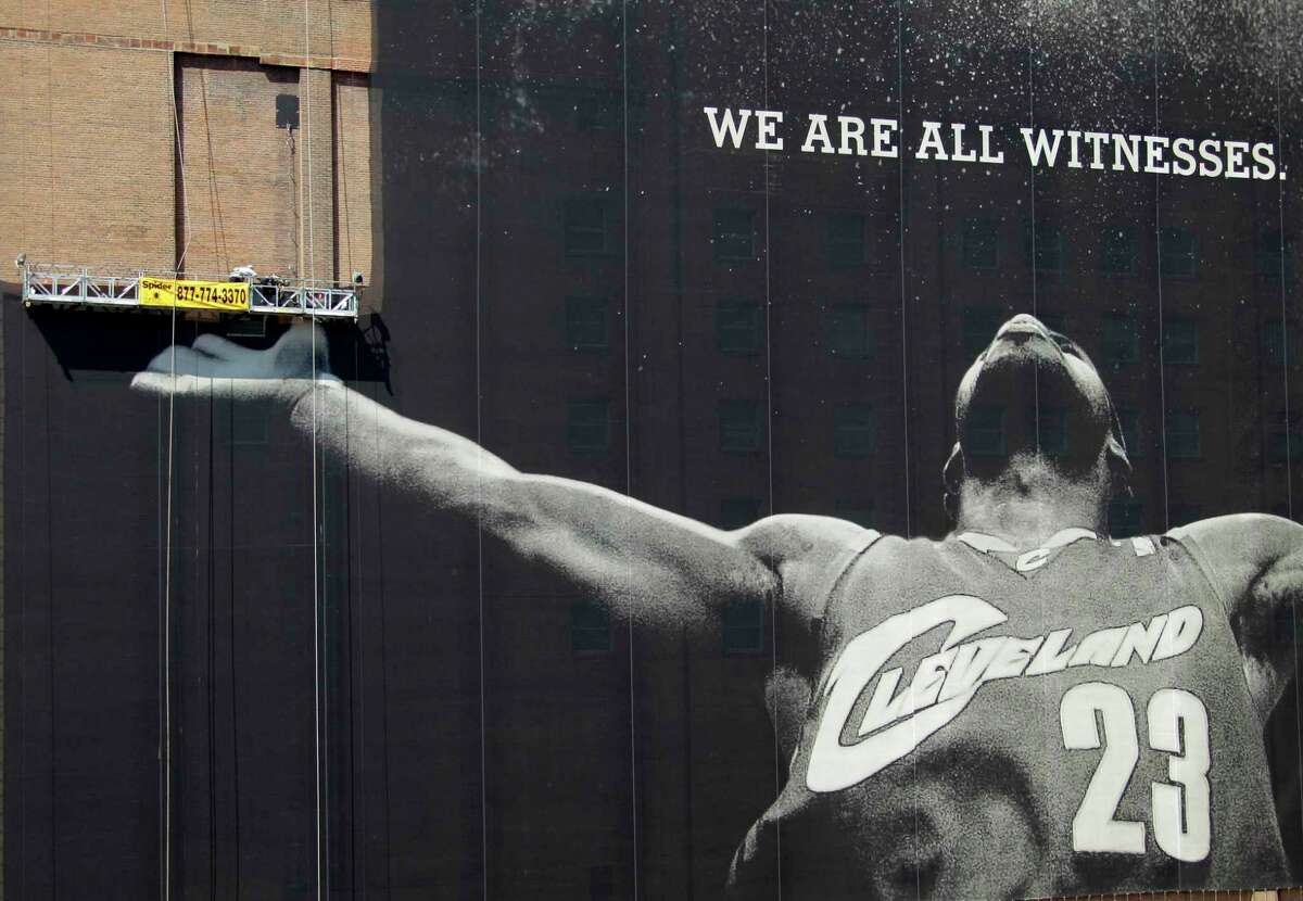 FILE - In this July 10, 2010, file photo, workmen remove a large mural of NBA basketball star LeBron James from a building in downtown Cleveland. For the second time in his career, James is saying goodbye to the Cleveland Cavaliers. The four-time NBA MVP announced Sunday night, July 1, 2018, that he has agreed to a four-year, $154 million contract with the Los Angeles Lakers. (AP Photo/Mark Duncan, File)