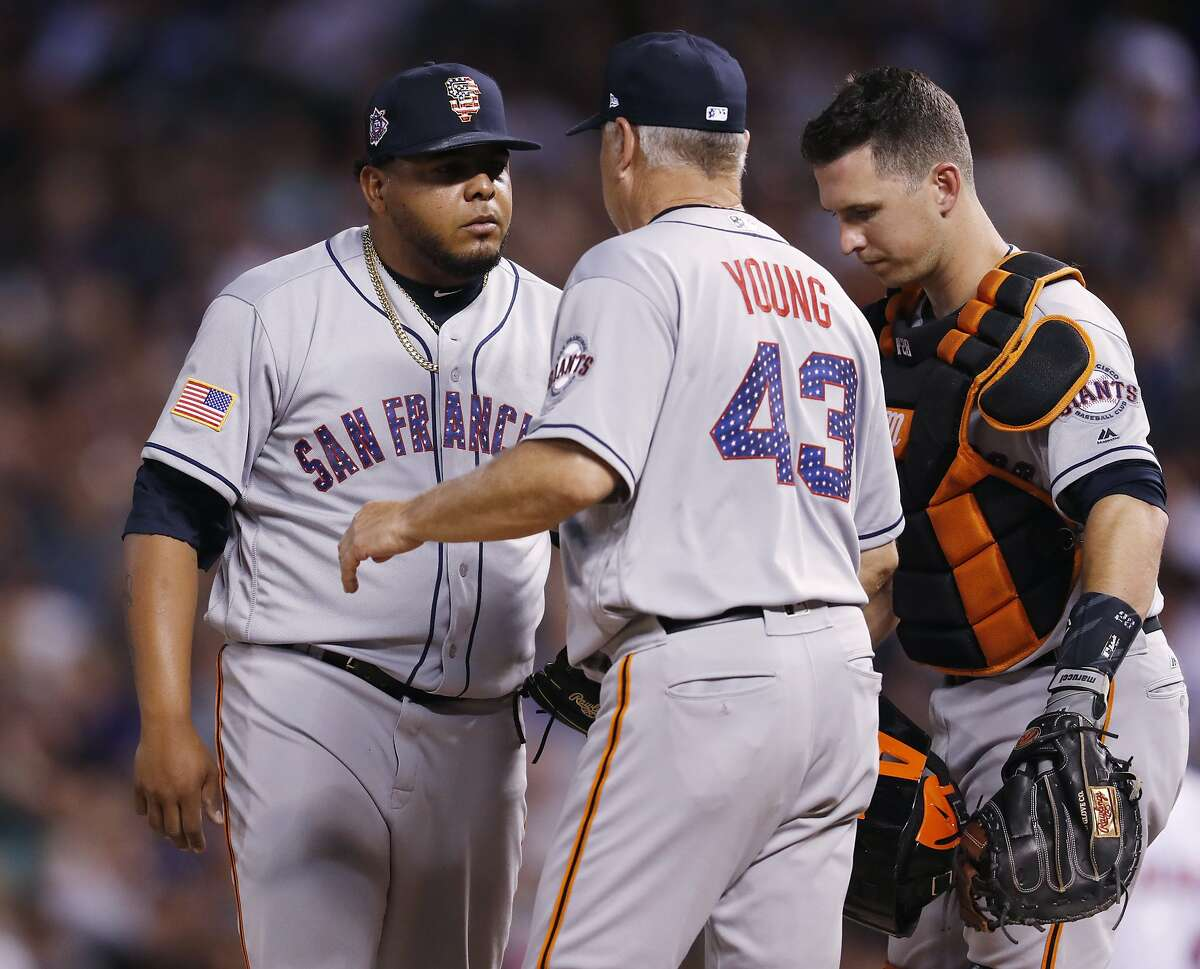 San Francisco Giants relief pitcher Reyes Moronta, left, covers with pitching coach Curt Young as catcher Buster Posey listens in after Moronta ave up a run on a double play hit into by Colorado Rockies' Trevor Story in the seventh inning of a baseball game Monday, July 2, 2018, in Denver. (AP Photo/David Zalubowski)