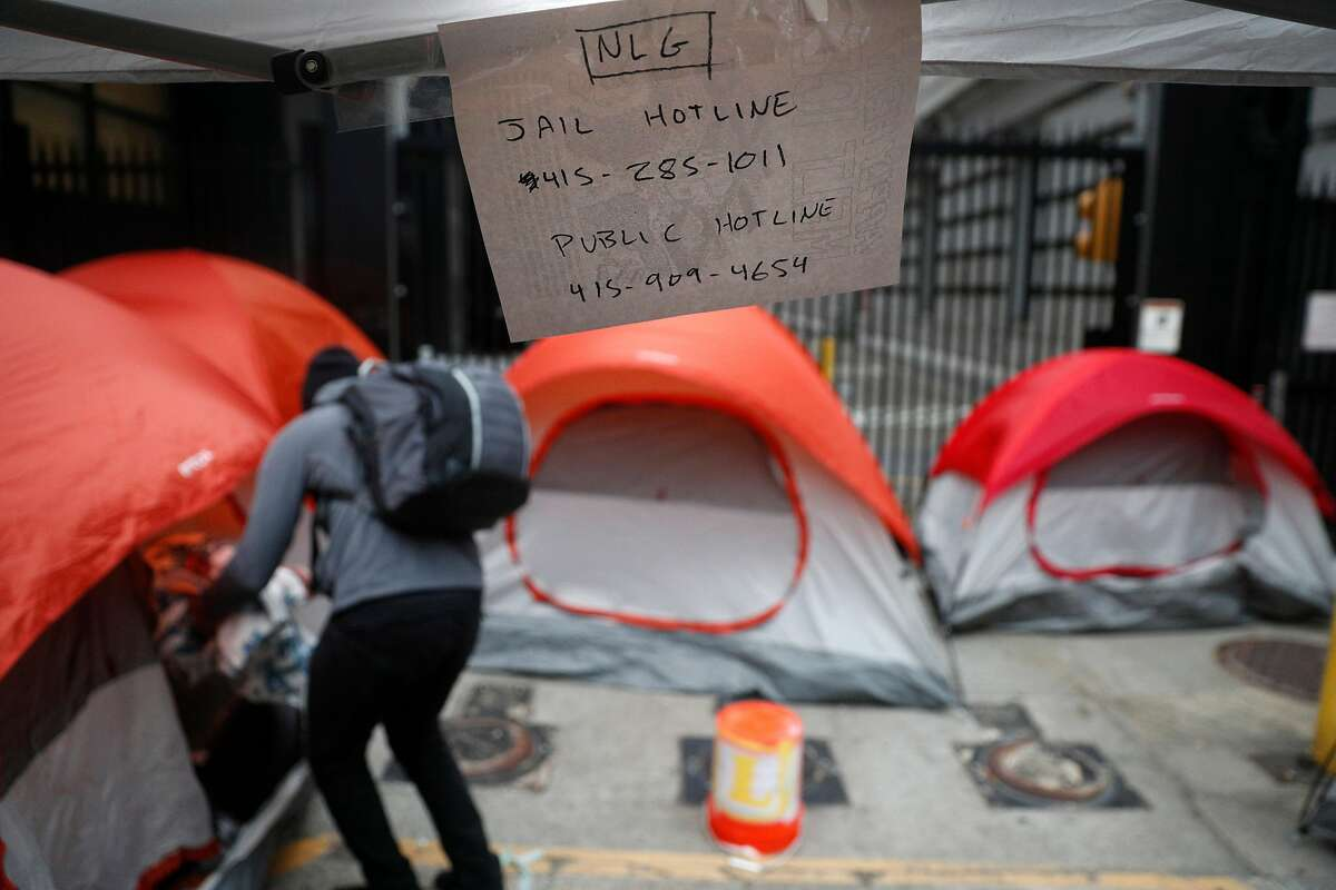 Phone numbers for the National Lawyers Guild are posted inside a camp that several dozen Occupy protesters set up outside the U.S. Citizenship and Immigration Services building to block Immigration and Customs Enforcement agents' access in San Francisco, Calif., on Monday, July 2, 2018.