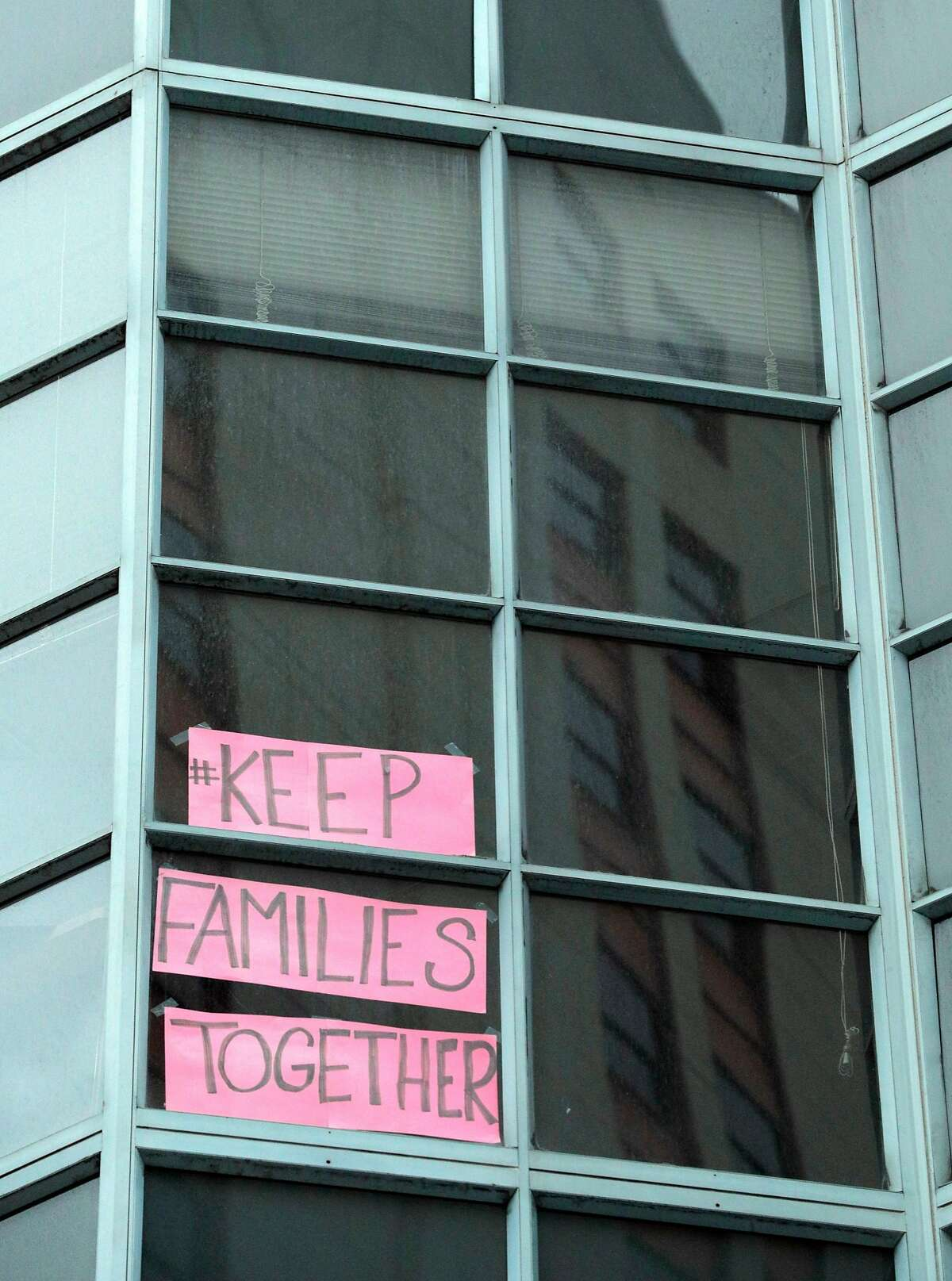 The U.S. Citizenship and Immigration buidling is reflected in an office building across the street with a sign reading,