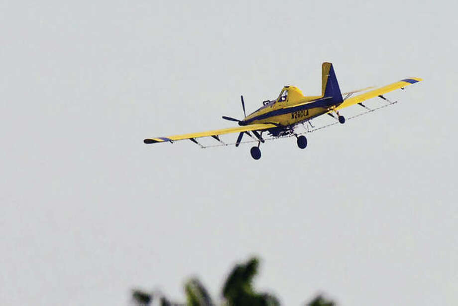 A crop duster flies closer to a field to do a round of spraying.
