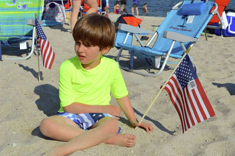 Alex Emden, 6, of Westport, plants a flag at the Westport Fireworks at Compo Beach, Monday, July 2, 2018, in Westport, Conn. Photo: Jarret Liotta / For Hearst Connecticut Media / Westport News Freelance