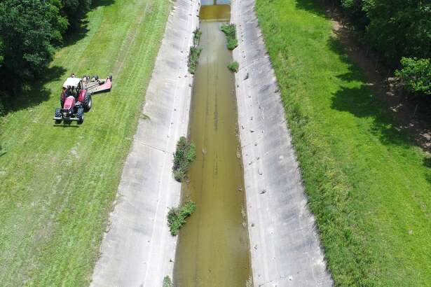 Drainage District 6 employees clear out a channel near Major Drive and Peveto Road in Beaumont Monday. DD6 Chief Engineer Doug Canant said the organization is running routine maintenance to keep drainage running. Photo taken Monday, 7/2/18
