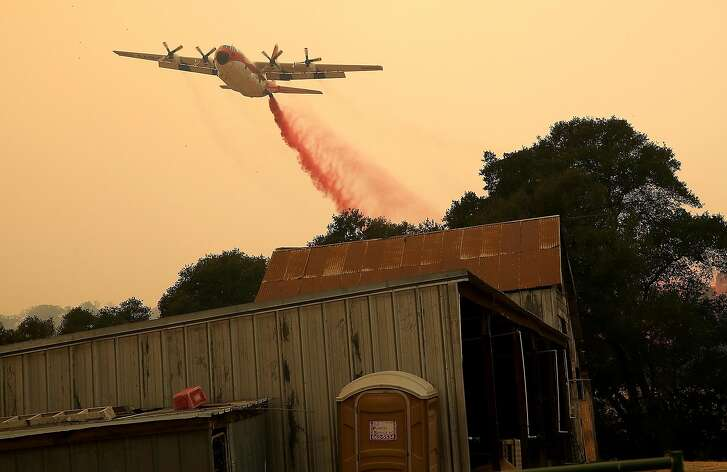 ESPARTO, CA - JULY 02:  A firefighting air tanker drops Foscheck fire retardant near a structure ahead of the County Fire on July 2, 2018 in Esparto, California.  The fast moving County Fire, that started on Saturday afternoon, has scorched nearly 45,000 acres as it continues to burn through dry grass and brush. The fire is currently 3 percent contained and has not burned any homes.  (Photo by Justin Sullivan/Getty Images)