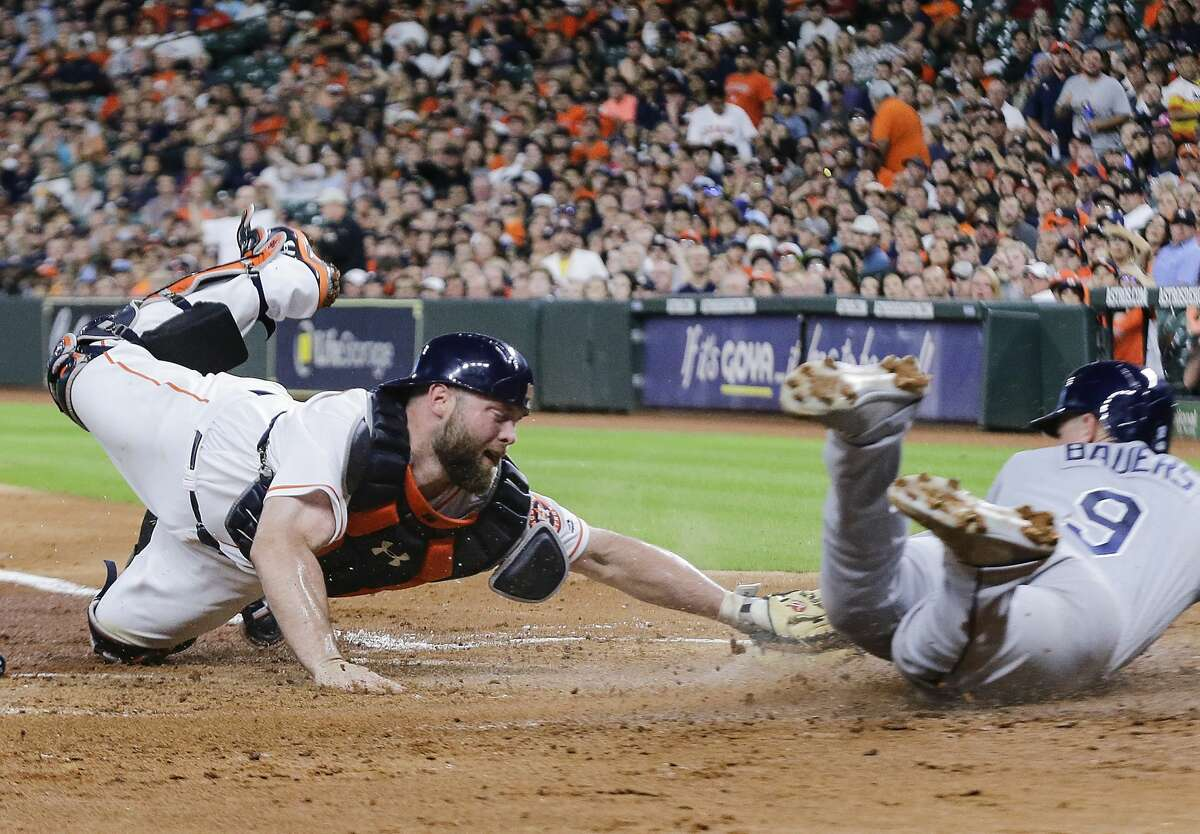 Houston Astros catcher Brian McCann misses a tag on Tampa Bay Rays first baseman Jake Bauers (9) as he scores on a Joey Wendel single during the third inning of a major league baseball game at Minute Maid Park on Monday, June 18, 2018, in Houston. ( Brett Coomer / Houston Chronicle )