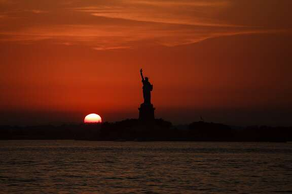 The sun sets behind the Statue of Liberty in New York, Sunday, July 1, 2018. (APPhoto/Andres Kudacki)