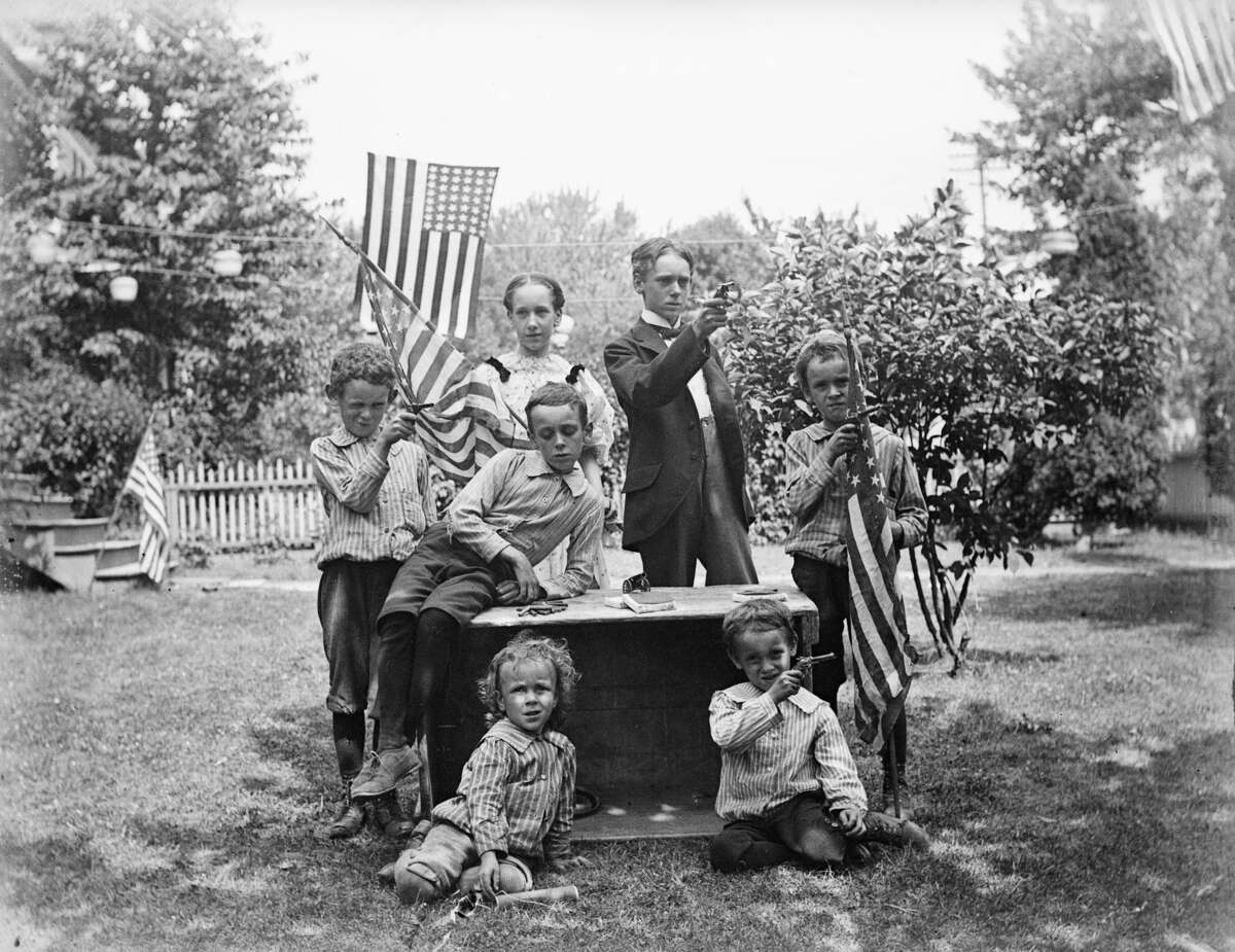 1880's Family group with pistols and flags ready for Fourth of July celebration.