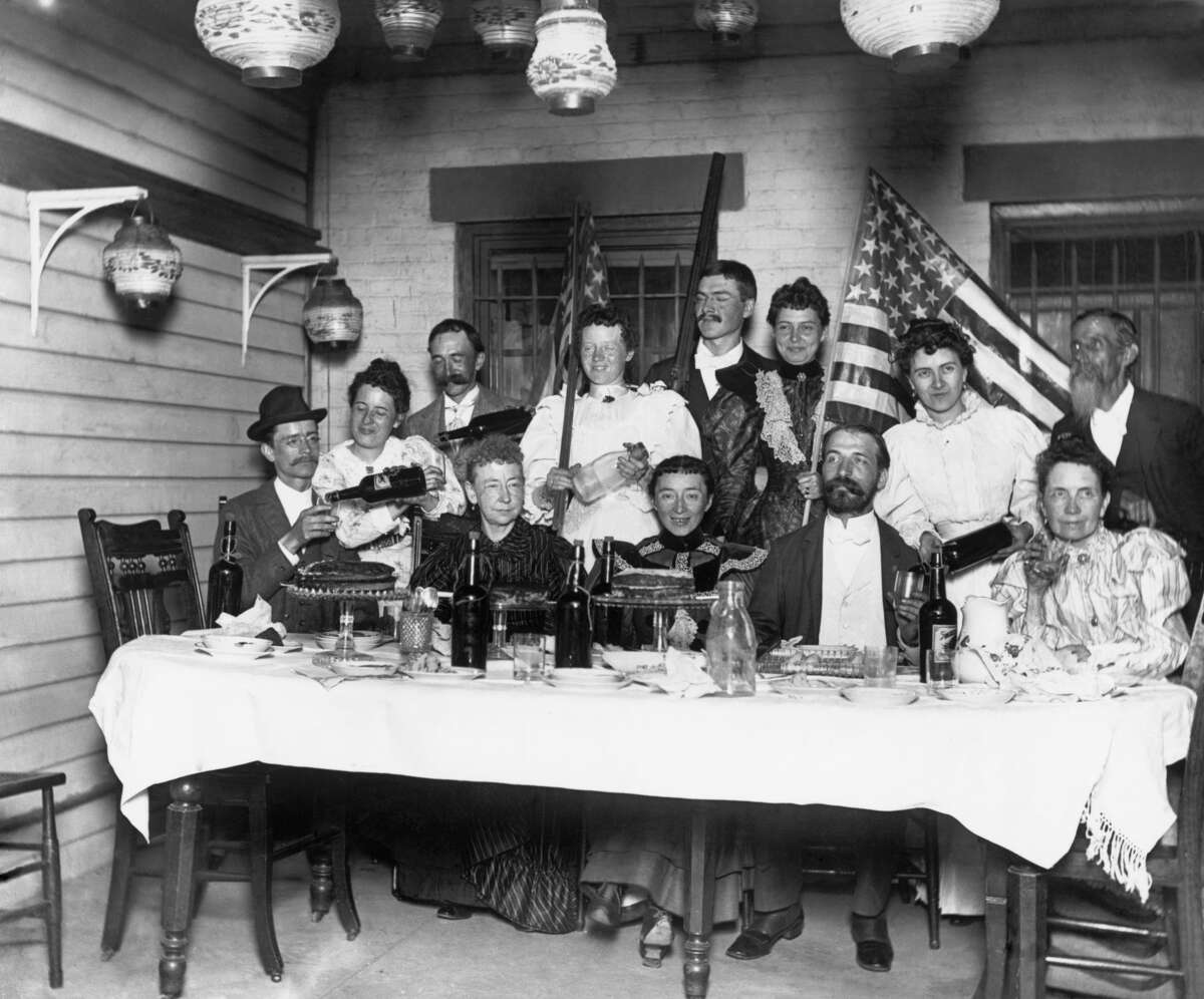 1894 A party in a middle class home. Plenty of drinks in evidence. The flags point to a Fourth of July celebration.