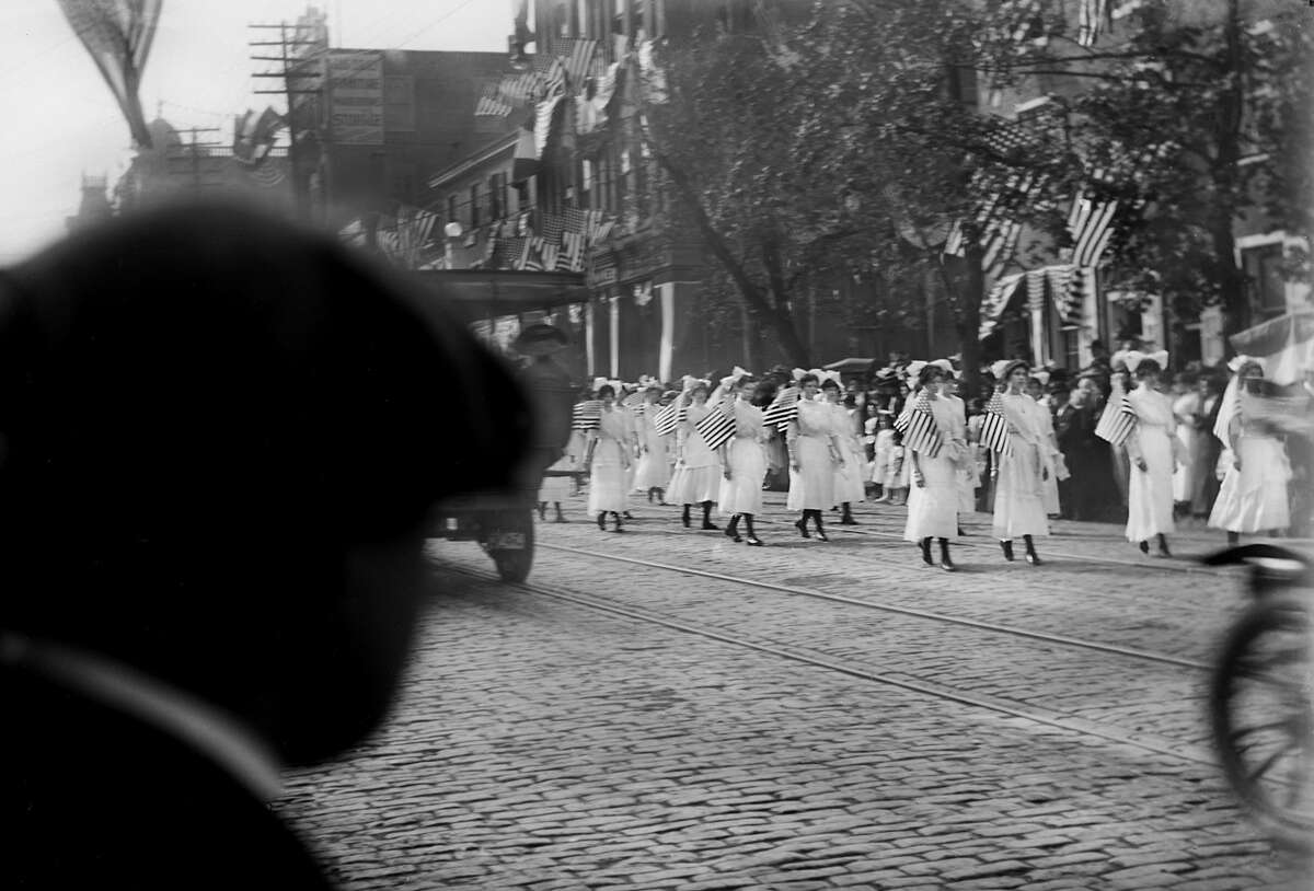 1905 Rear view of a man watching women in a Fourth of July Parade.